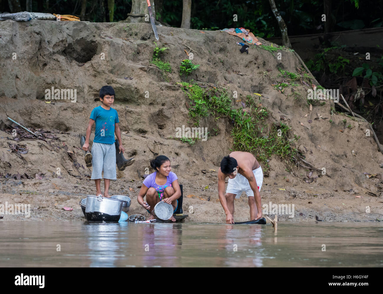 A native Kichwa family wash and clean by Rio Napo in the Amazons. Ecuador, South America. - Stock Image