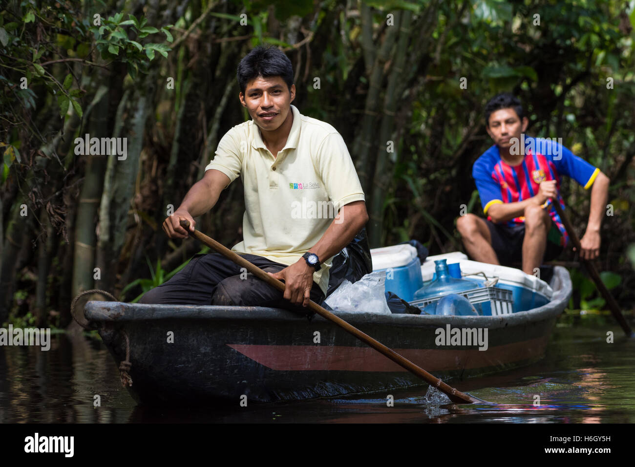 Native Kichwa people deliver goods on a canoe in the Amazons. Yasuni National Park, Ecuador. - Stock Image