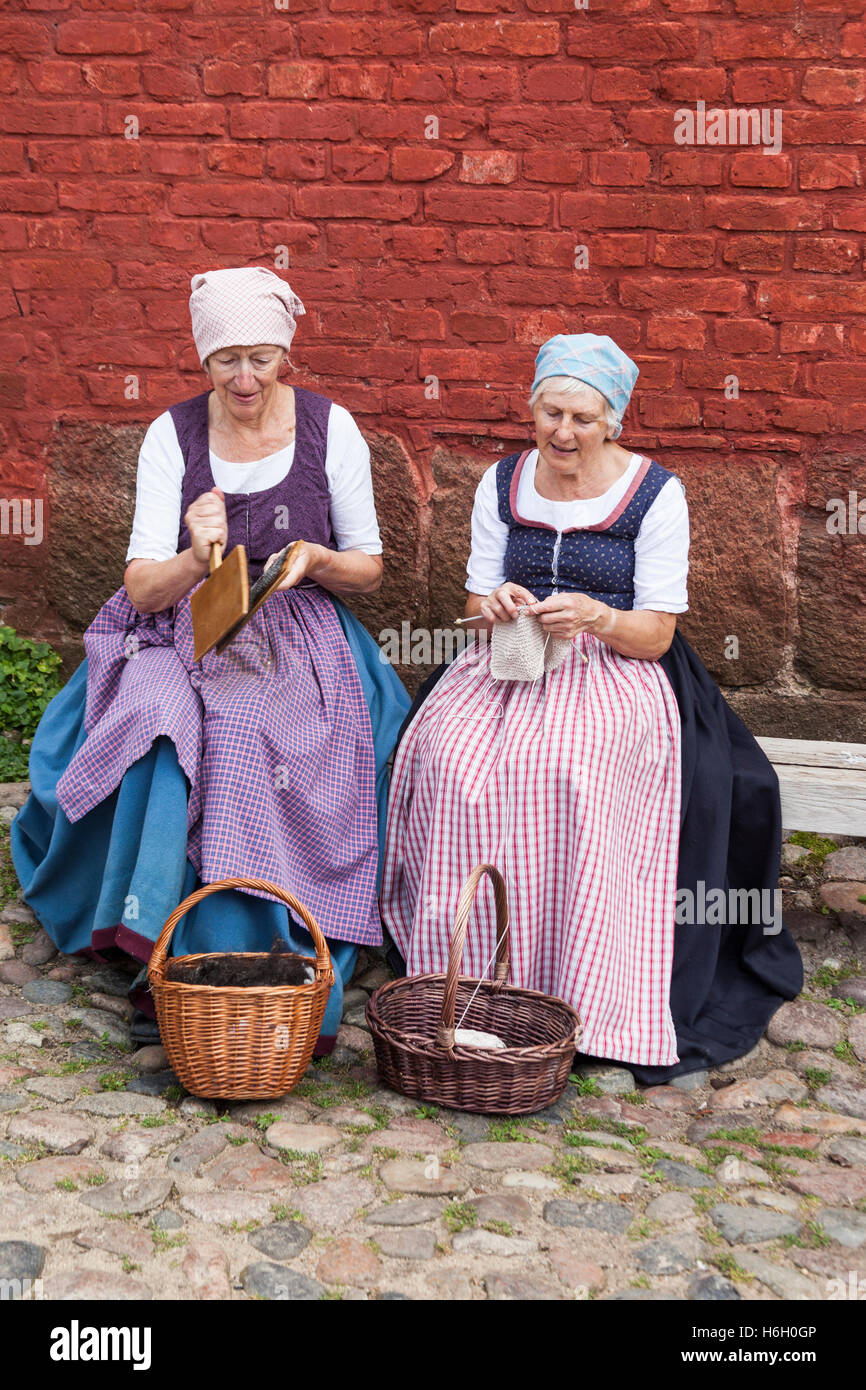 Two ladies dressed in traditional costume carding and knitting, Den Gamle By, Aarhus, Denmark - Stock Image
