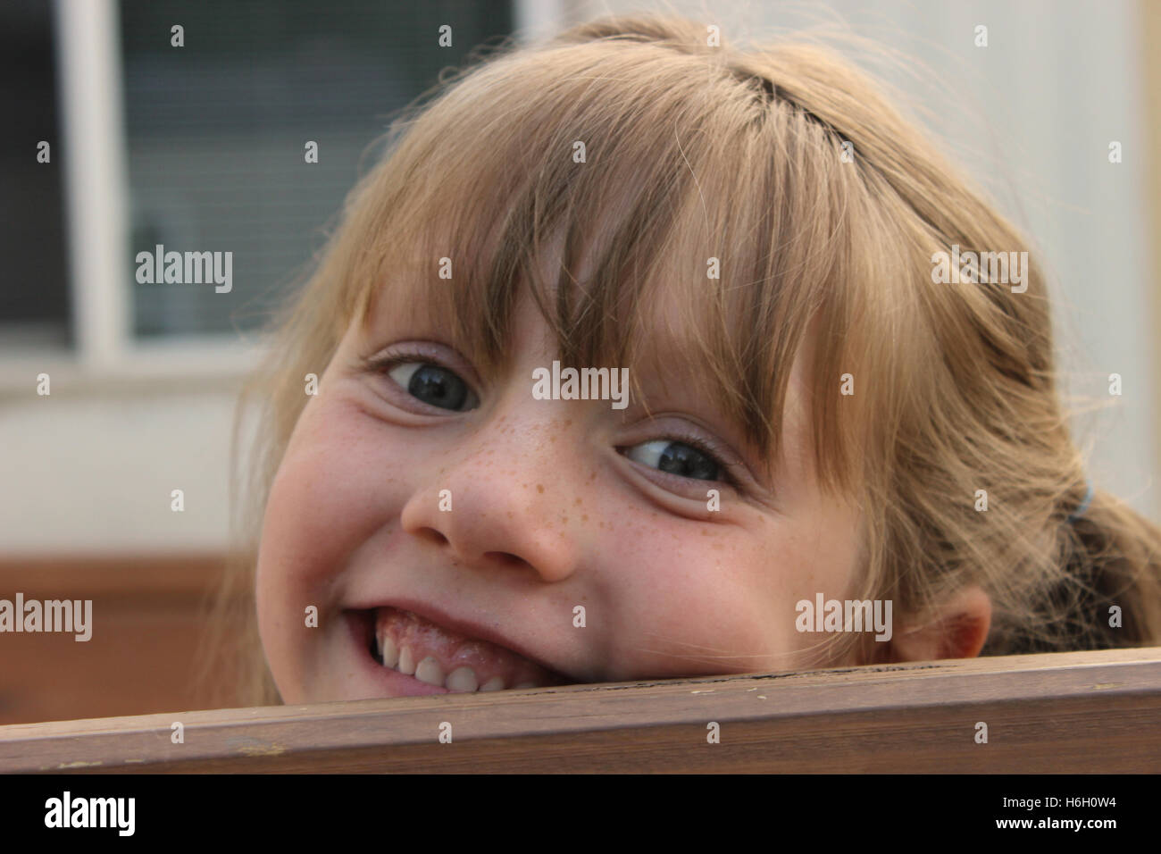 b close up of young freckled girl peeking over wooden rail and  smiling with teeth - Stock Image
