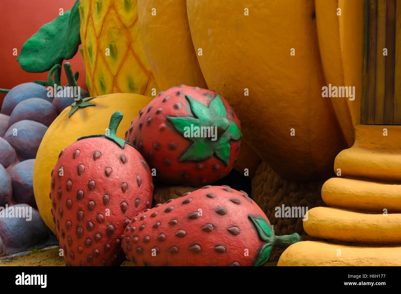 Fruit modelled in cement at an amusement part - Stock Image