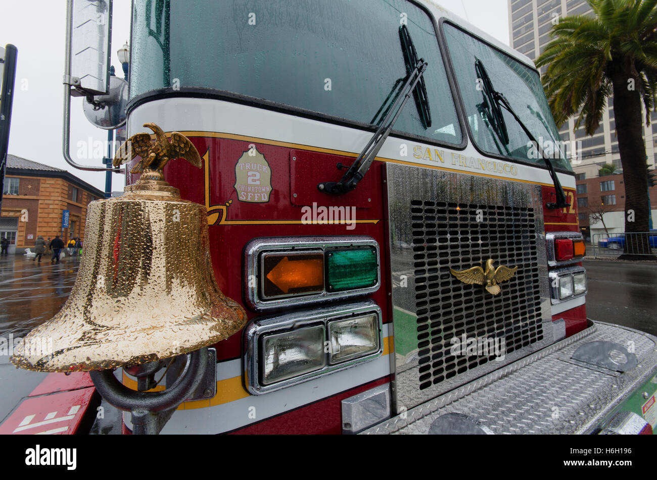 A bright gold bell adorns the front of a San Francisco ladder truck sitting in the rain on the Embarcadero. - Stock Image