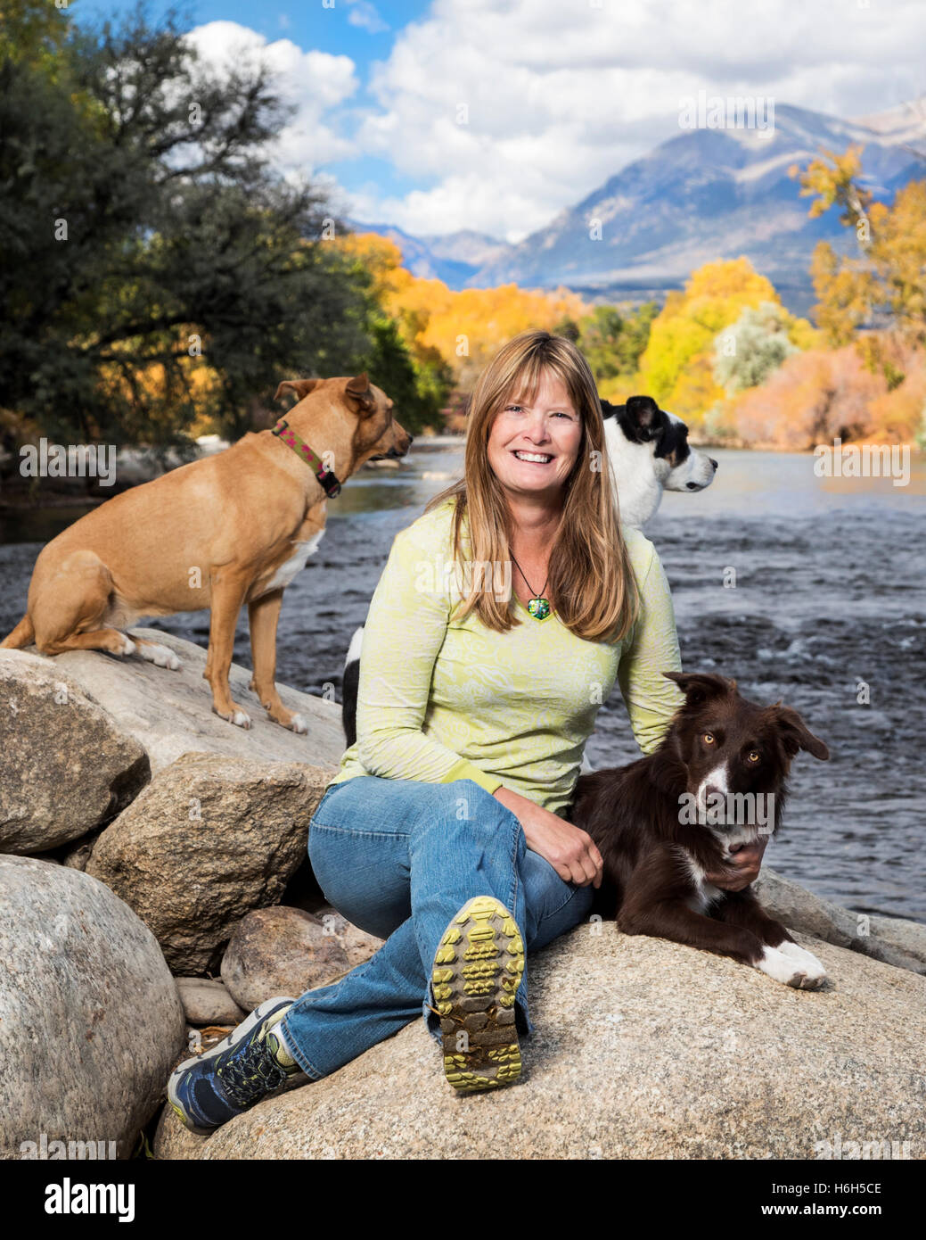 Outdoor portrait of attractive woman with her three dogs alongside the Arkansas River; Salida; Colorado; USA - Stock Image