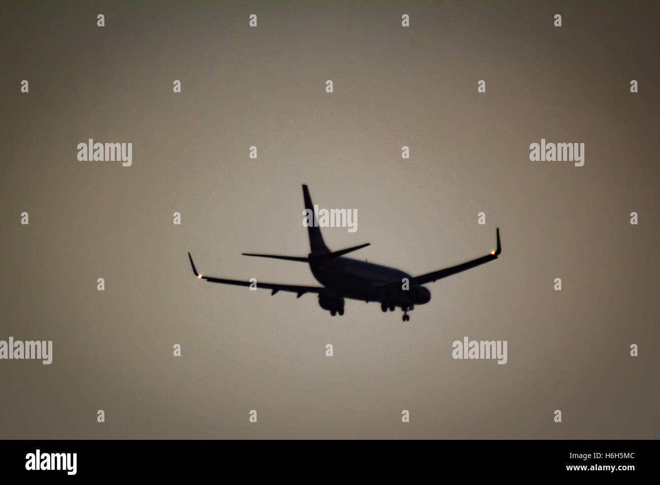 Silhouetted Jet In Flight - Stock Image