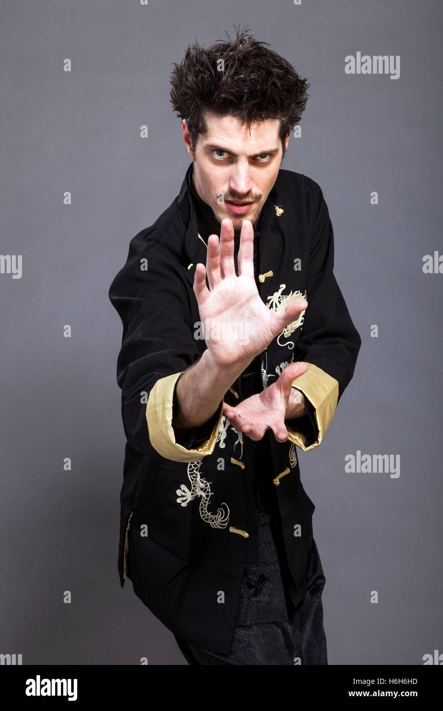 Studio shot of a man in his late twenties, wearing traditional chinese clothing and Kung-Fu posture. - Stock Image