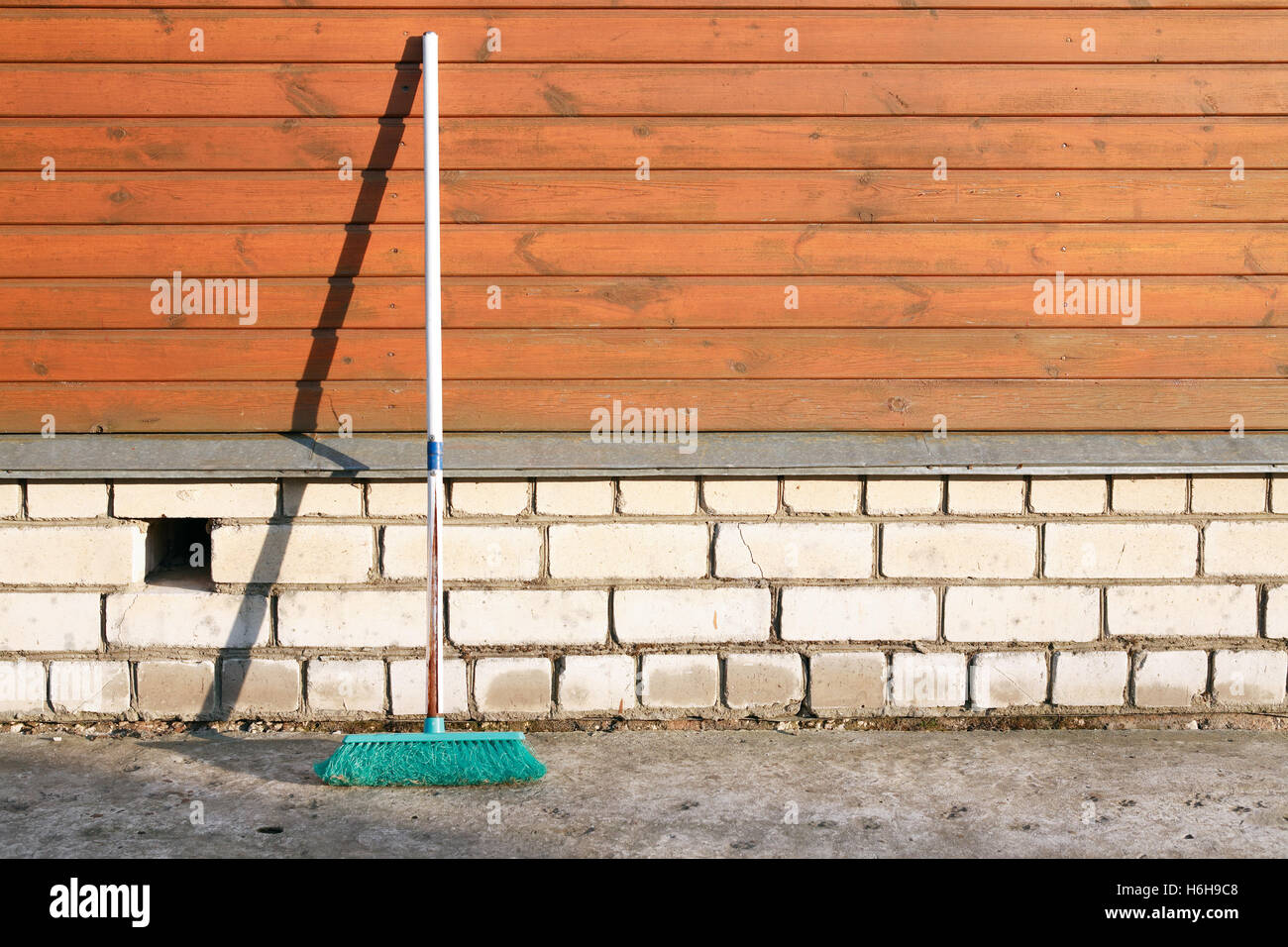 Old mop near wooden wall of house with shadow - Stock Image