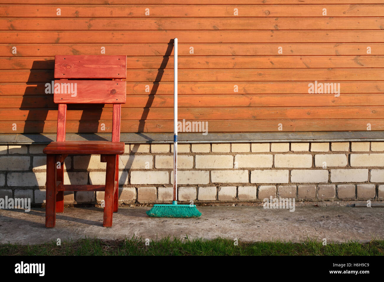 Time of rest. Old mop near chair against wooden wall of house - Stock Image