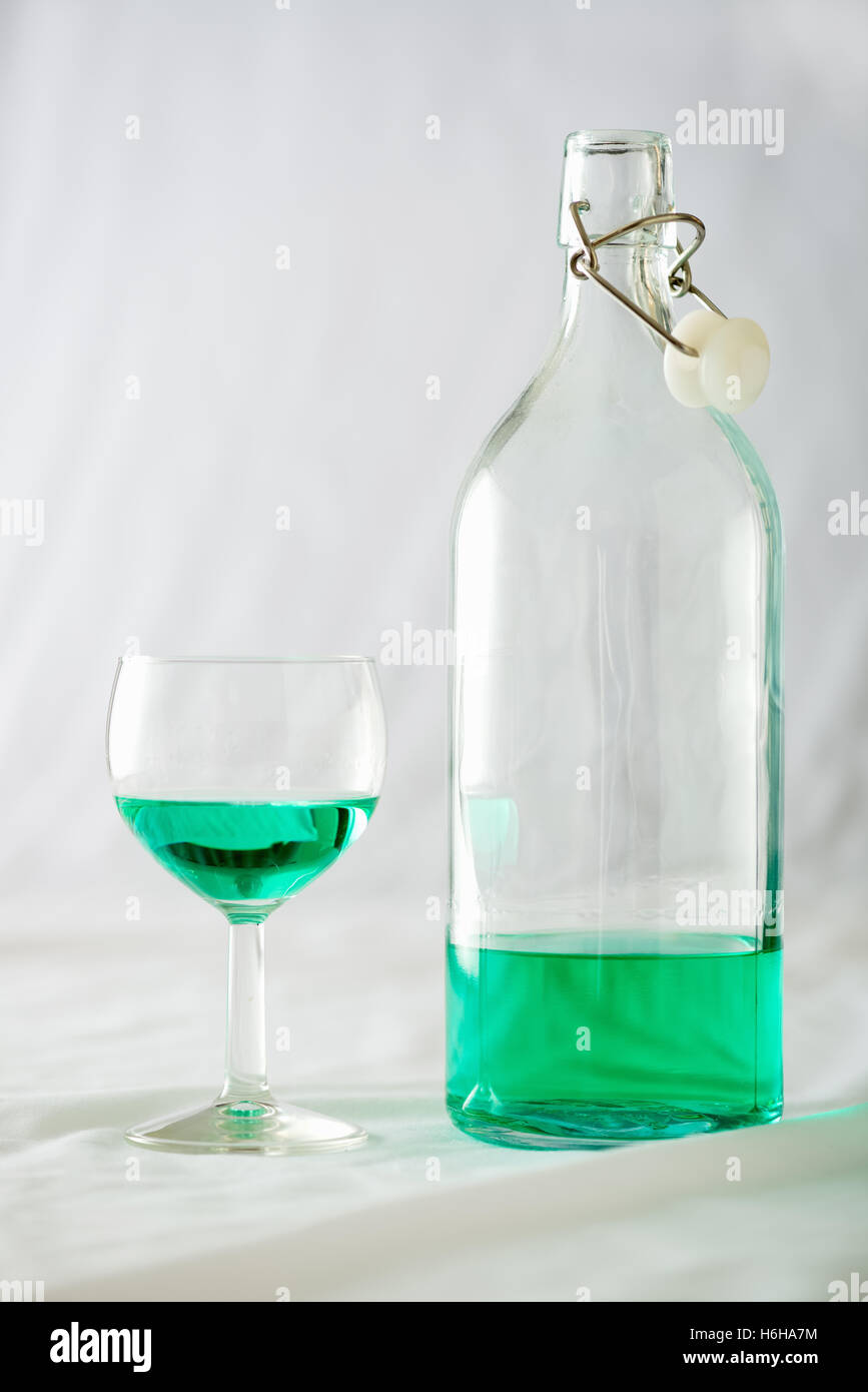A glass and bottle of absinthe set on a white background Stock Photo
