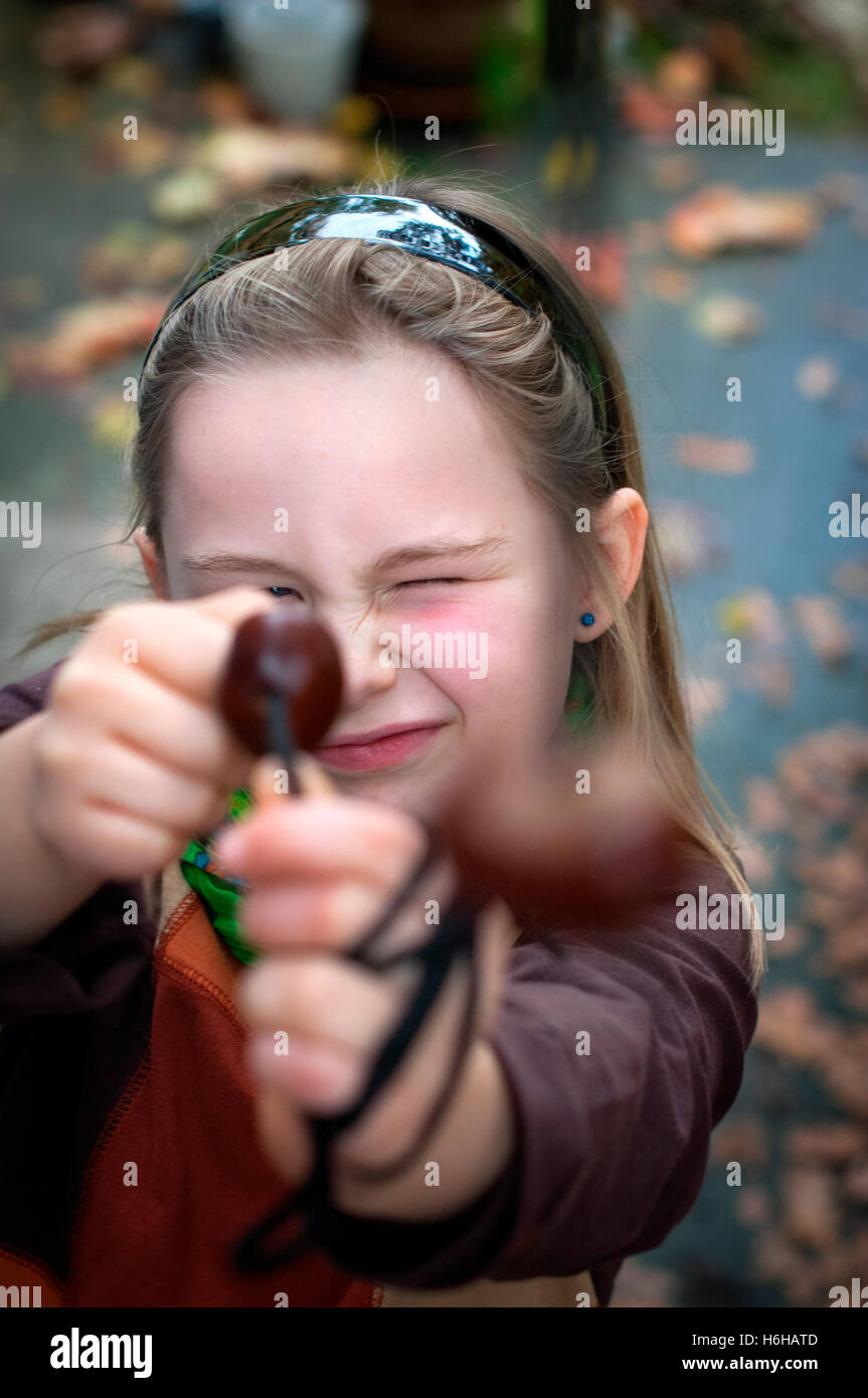 A young girl playing conkers. - Stock Image