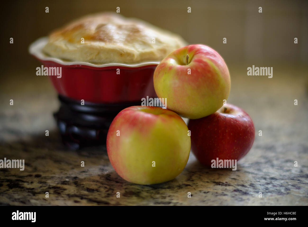 Apples with a apple pie on a kitchen counter. - Stock Image