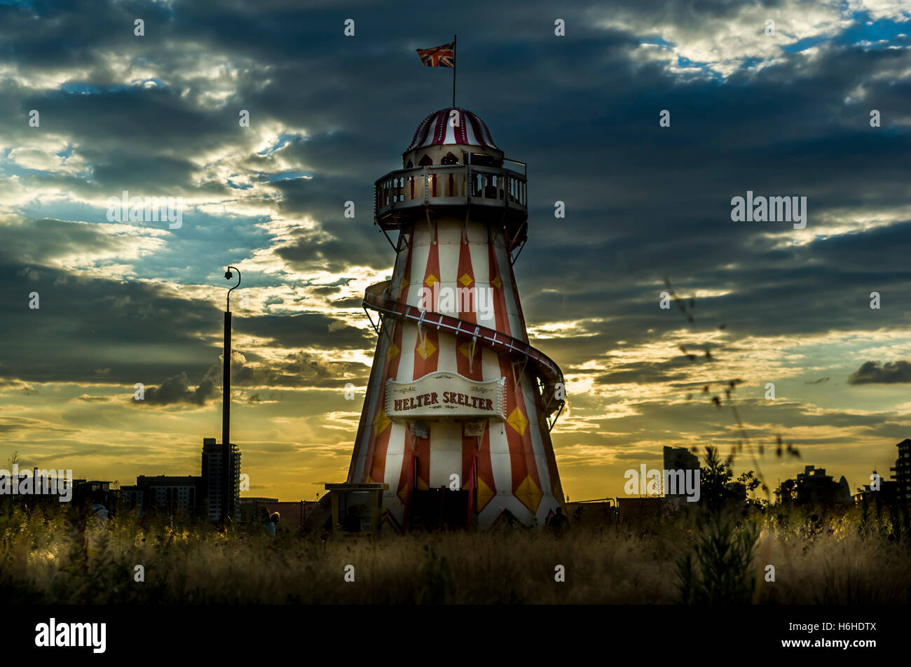 A dark and moody scene, with dramatic sky and a helter skelter, at Greenwich, London. - Stock Image