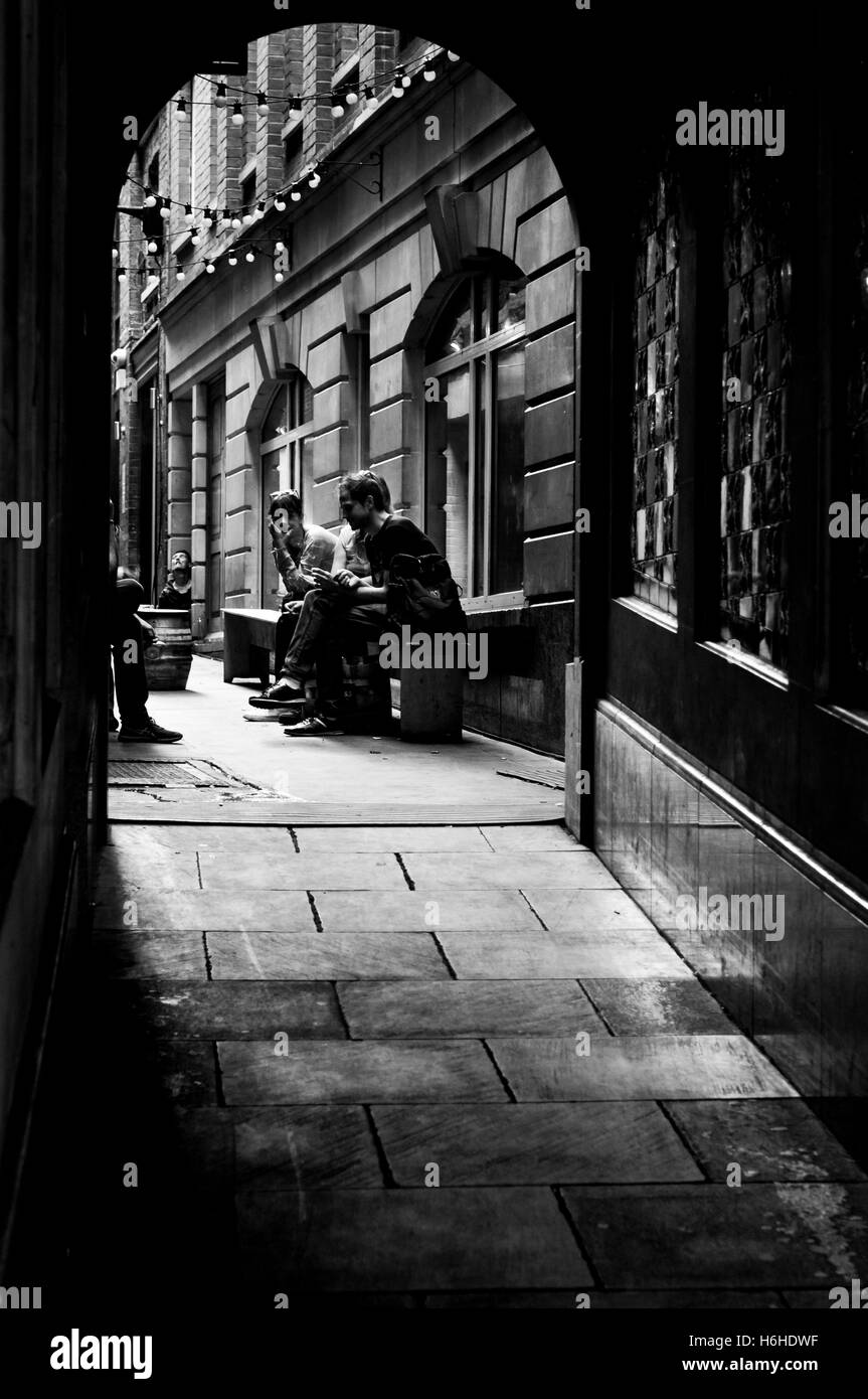 Moody, black and white image of a dark, backstreet, alley in London, with people sitting at the end talking. - Stock Image