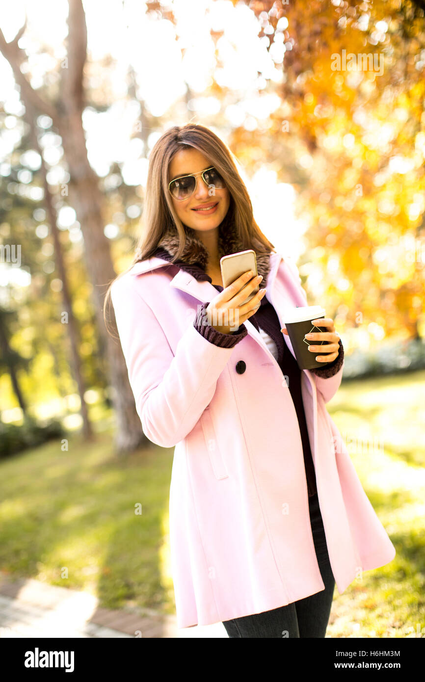 Young woman in the pink coat talking over the smartphone and holding coffee to go in hand at autumn park - Stock Image