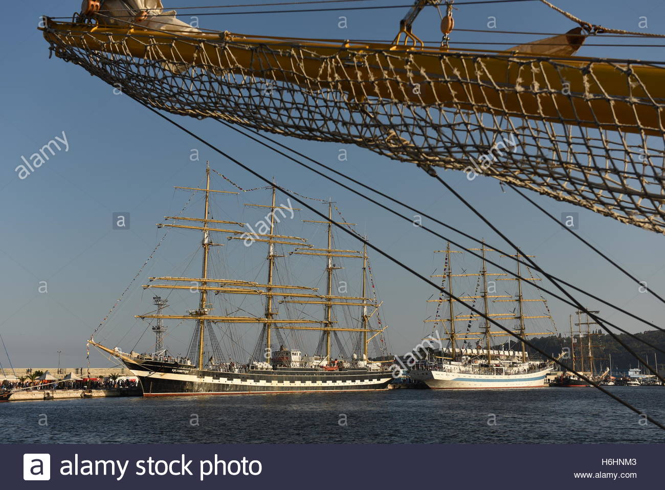 Tall ships with sails up at backdrop and ropes and nets rigging on foreground - Stock Image
