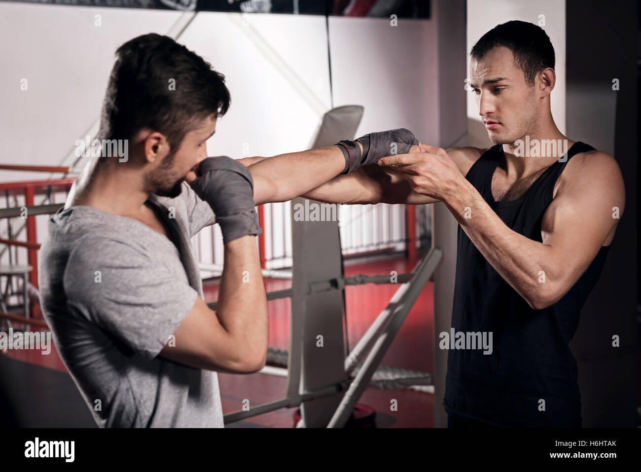 Trainer teaching a man how to box - Stock Image