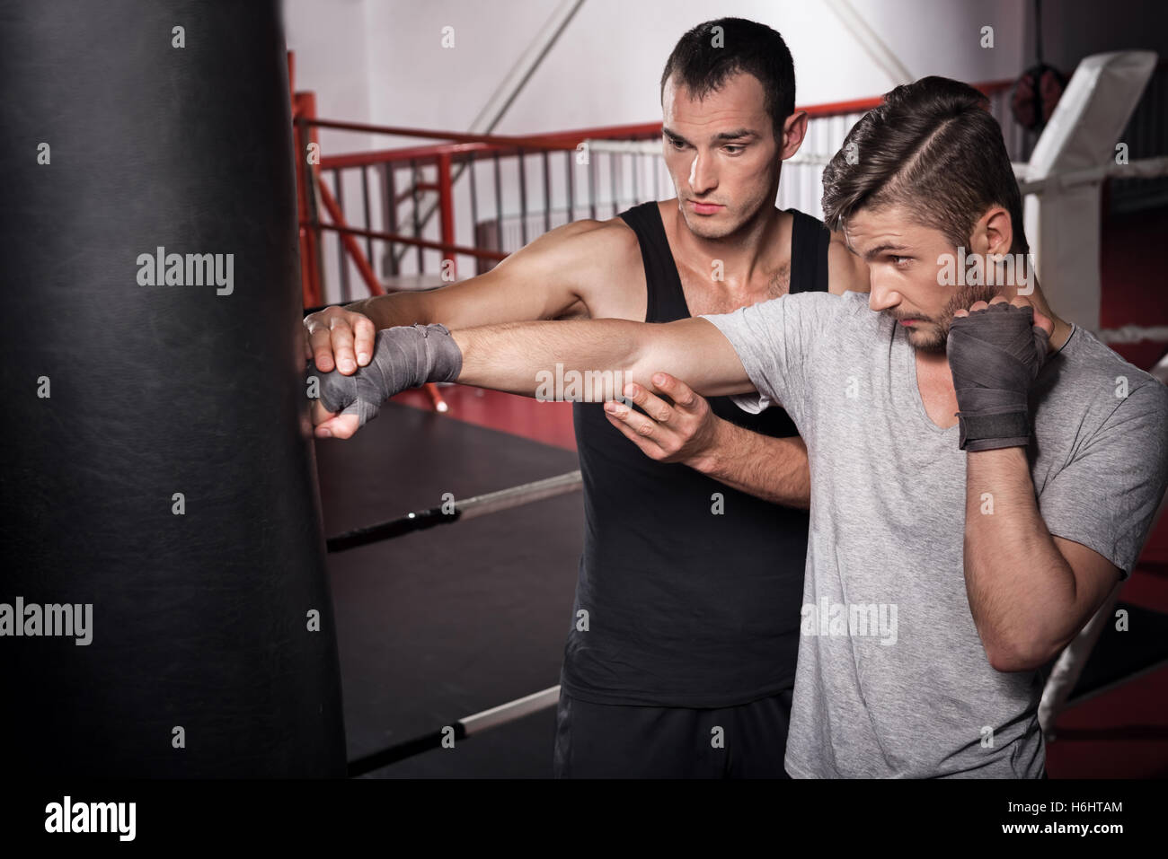 Trainer teaches how to punch a bag - Stock Image