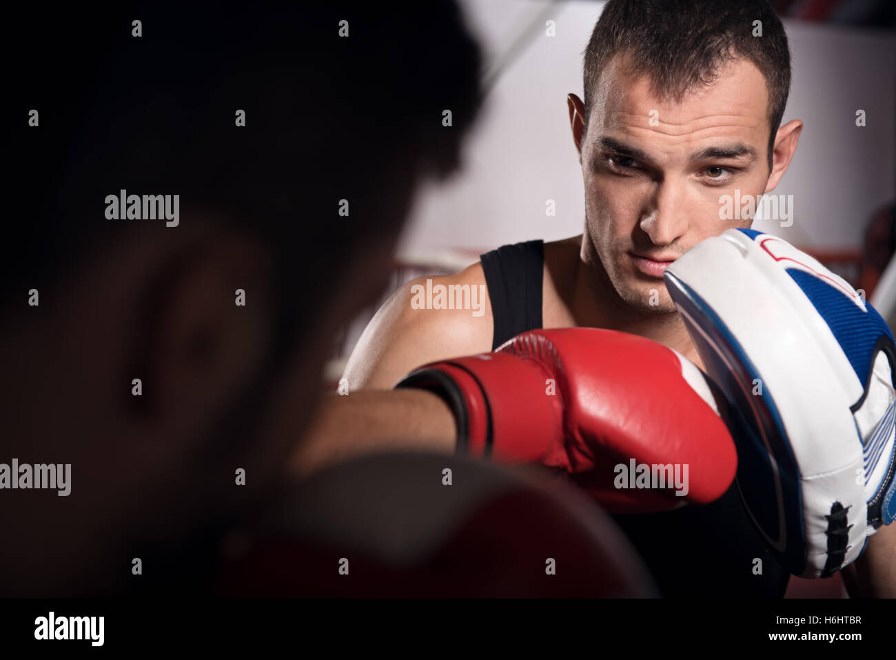 Young trainer holding boxing pad Stock Photo