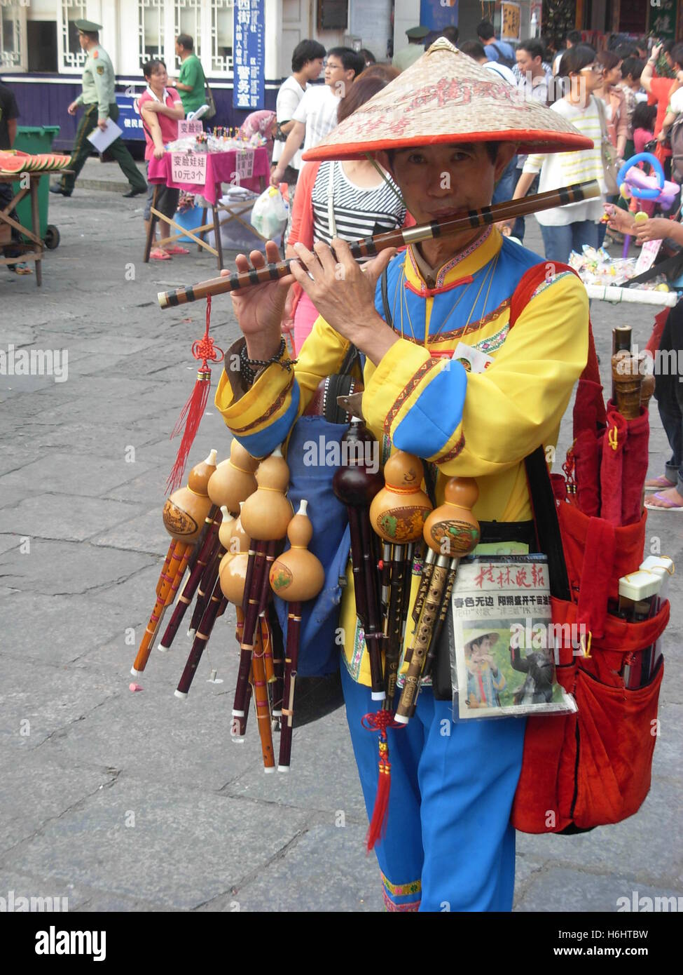 Chinese man playing and selling flute on the streets of Yangshuo, Guangxi province, China Stock Photo