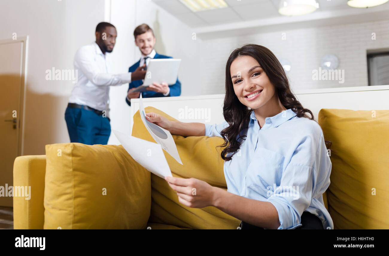 Positive charming businesswoman sitting on the sofa - Stock Image