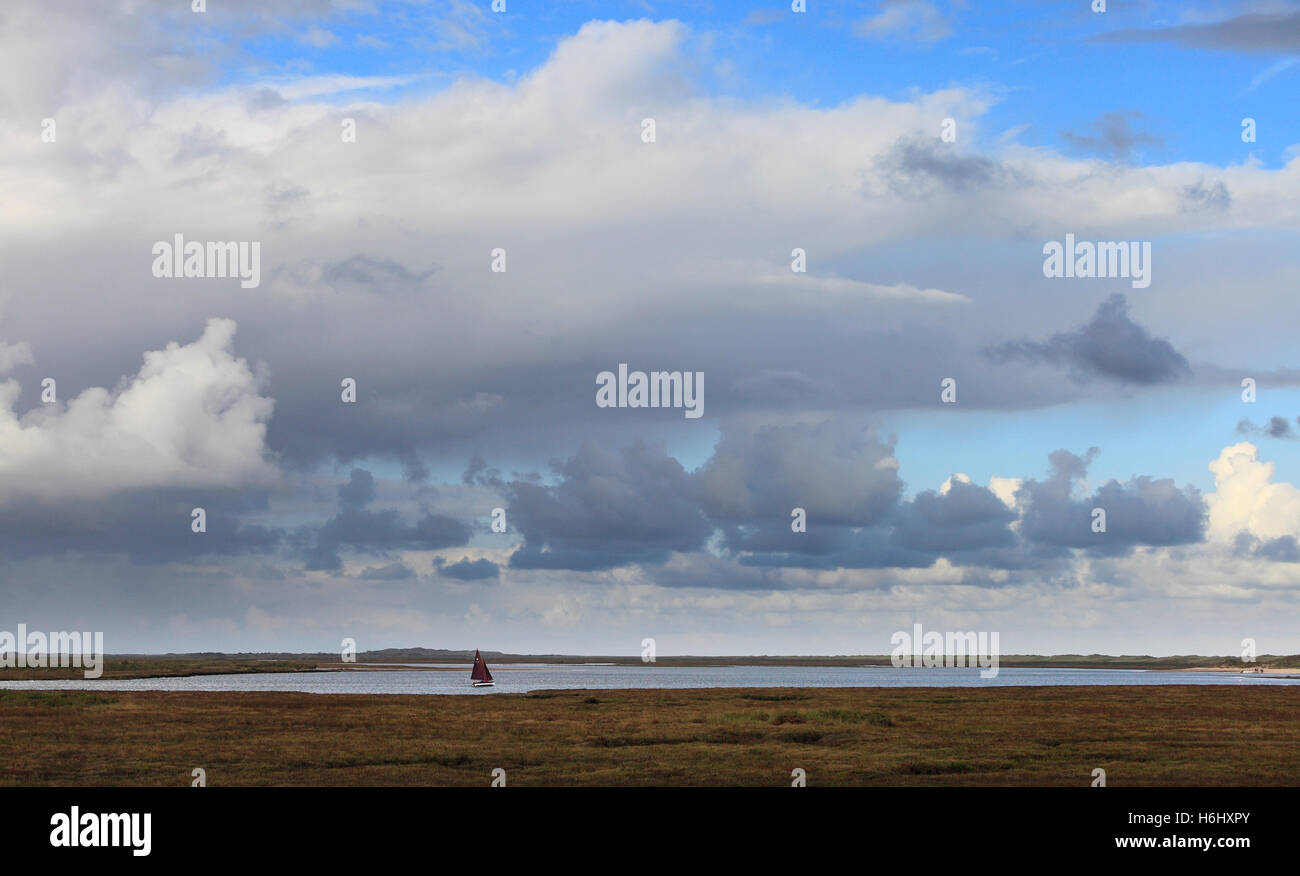 Sailing boat traveling from the harbour at Burnham Overy Staithe to Scolt Head. - Stock Image