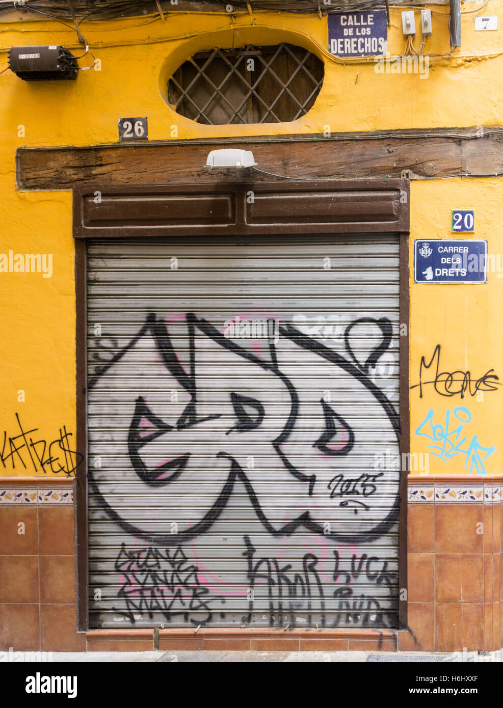 Spray painted graffiti on a closed shutter and street signs in Catalan and Spanish - Stock Image