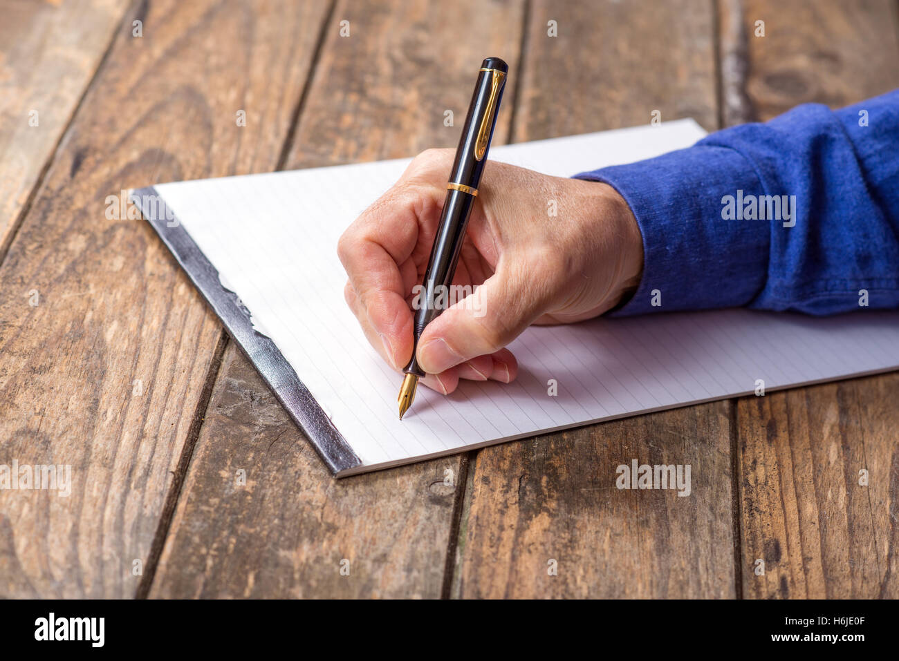 man's hand writing with a fountain pen. wooden background Stock Photo