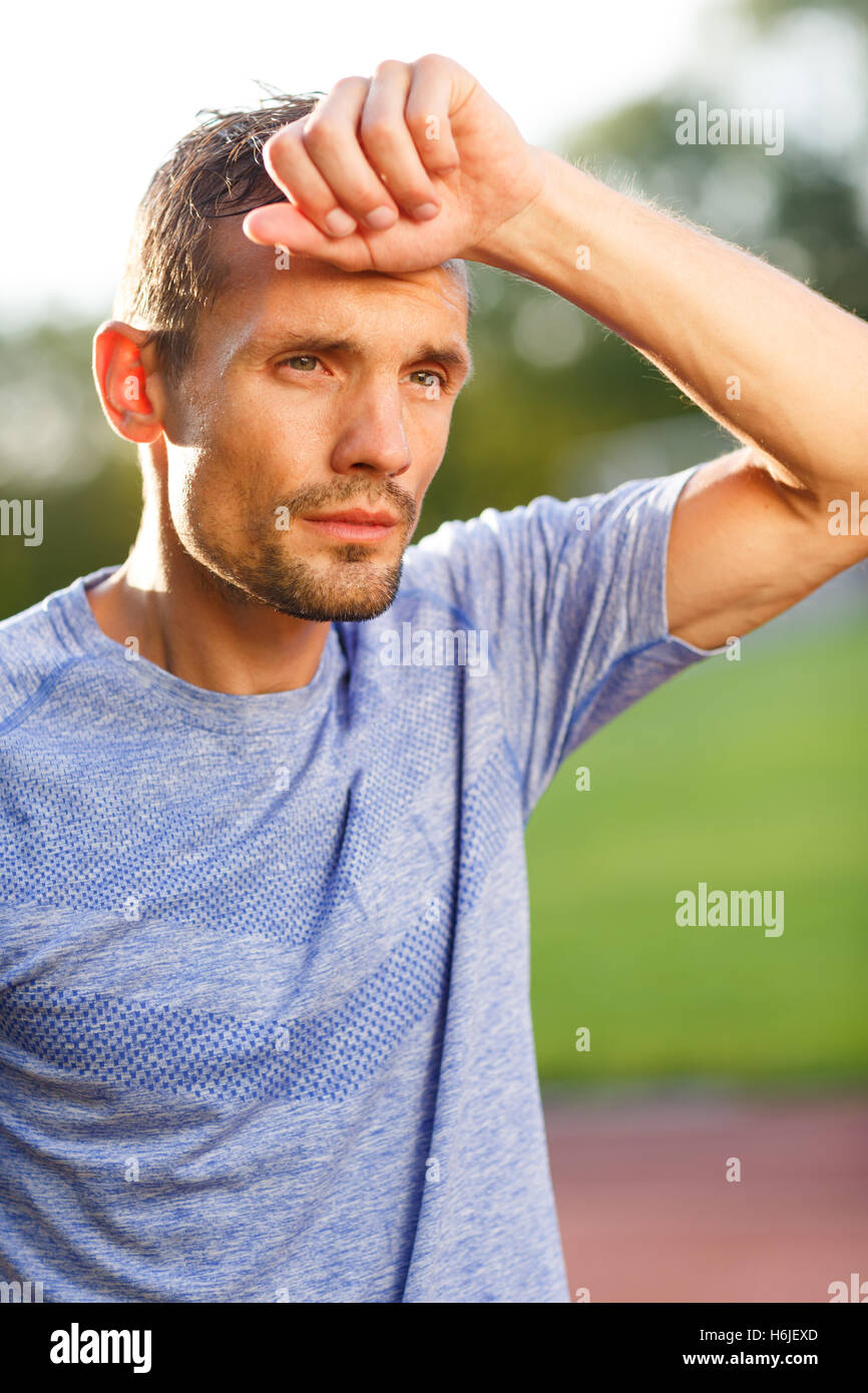 Tired in training athlete wiping his forehead on nature - Stock Image