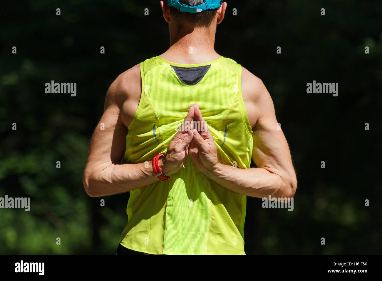 Male runner performing Pashchima (Pascima) Namaskarasana. Hands Behind The Back. - Stock Image
