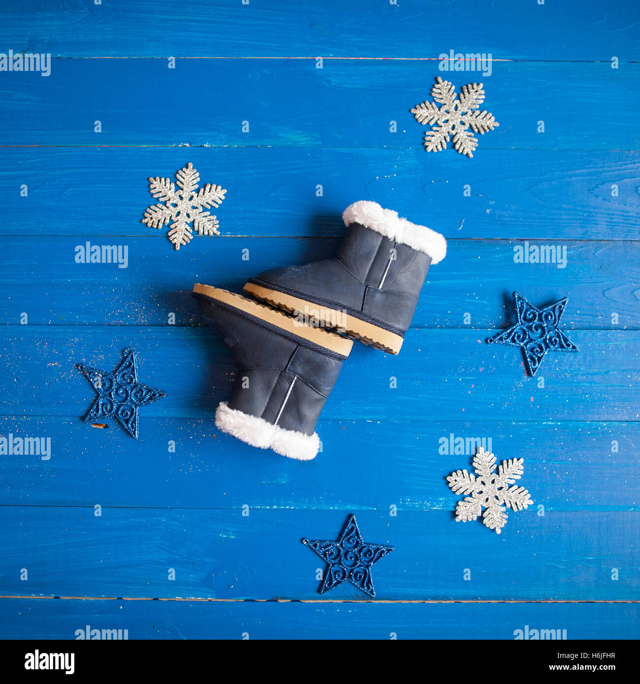 winter children's clothing, fur boots on a blue wooden background. - Stock Image