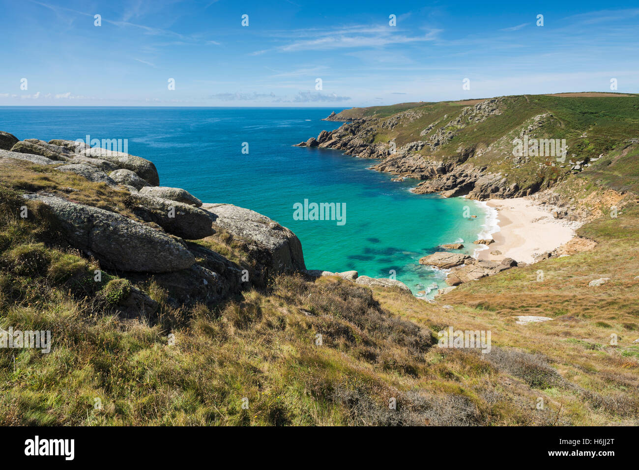 Turquoise lucent sea at cliffs and sandy Porth Chapel Beach on Penwith Peninsula south coast in summer, Cornwall, - Stock Image