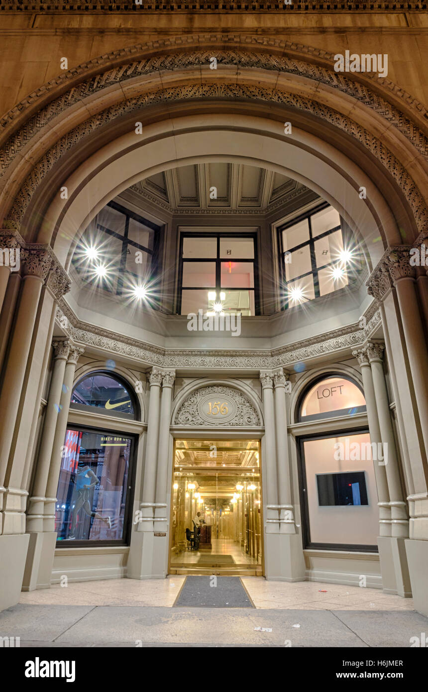 Portico and entrance of 156 Fifth Avenue at night, with windows of Nike and Loft stores. - Stock Image