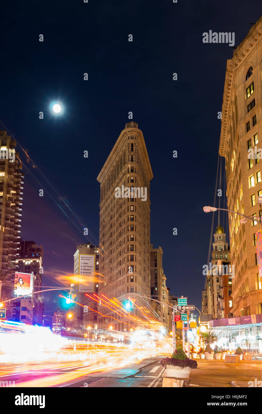 Flatiron Building and 5th Avenue at night with headlight trails, New York. - Stock Image
