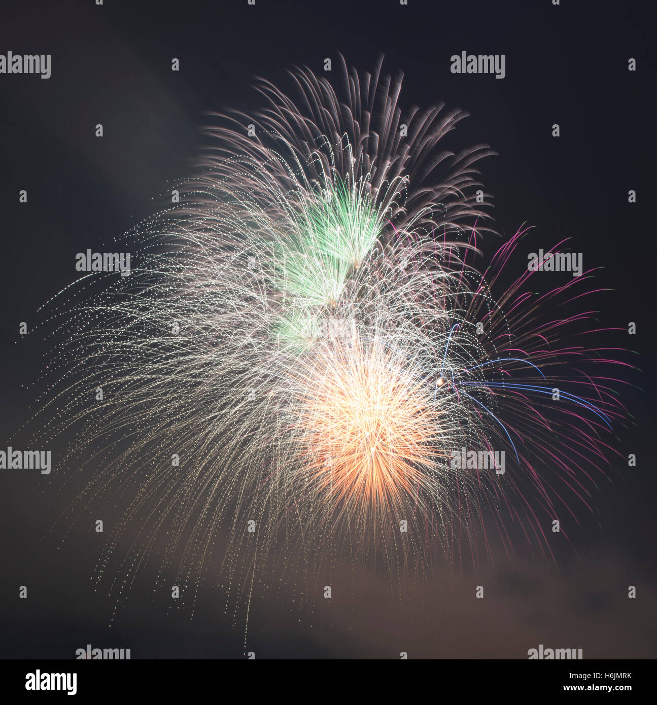 Exploding fireworks in green, orange, red and blue in a smokey night sky - Stock Image