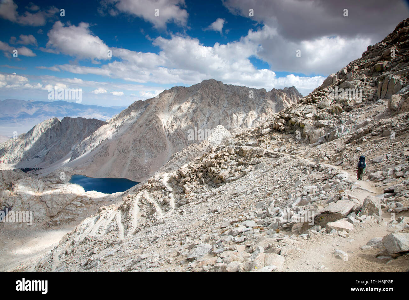A single hiker on the long, John Muir Trail leading up to Mt. Whitney in the Sierra Mountains of California. - Stock Image