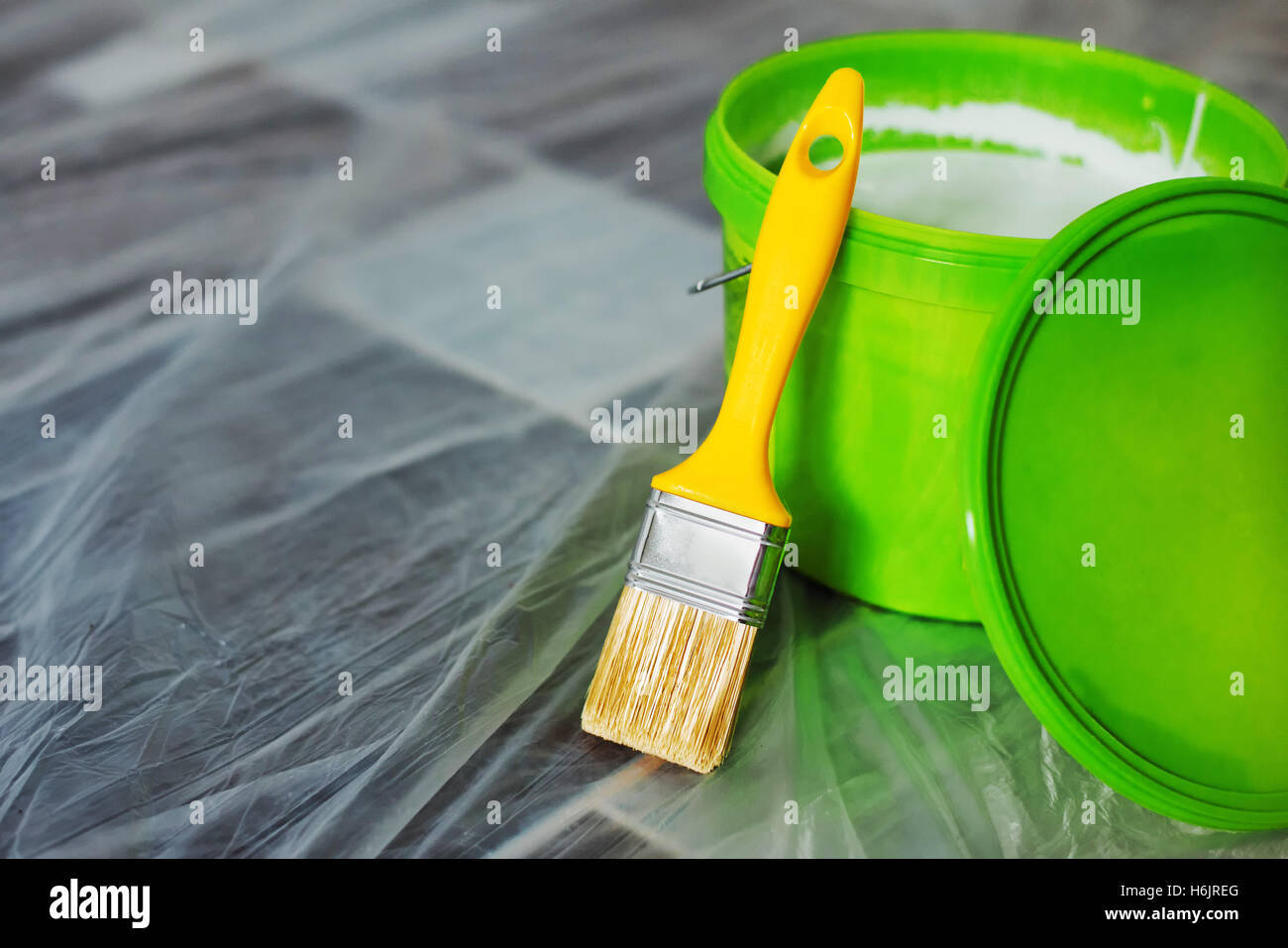 Yellow paint brush and green bucket on the floor, ready for housework project and walls redecoration - Stock Image