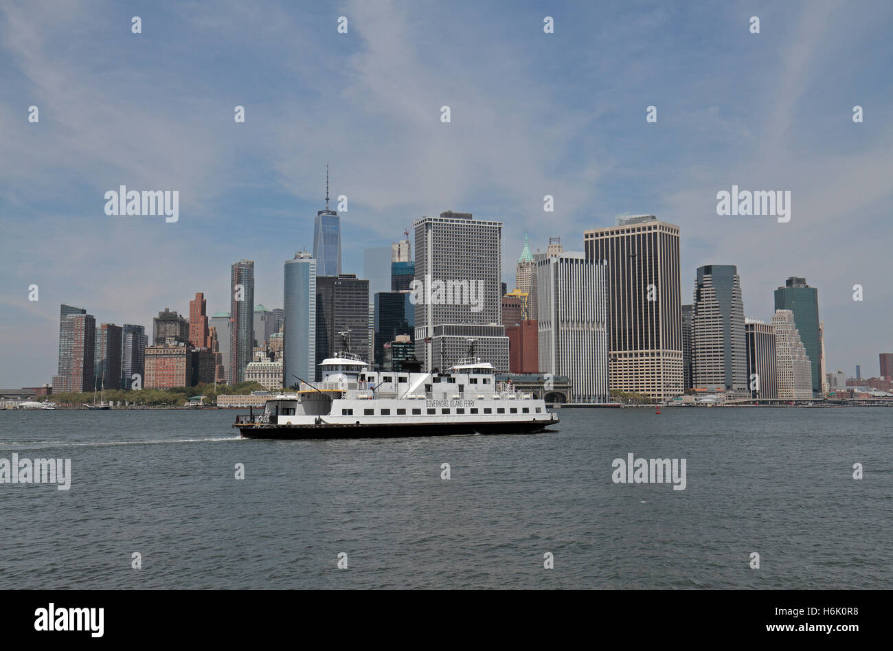 a governors island ferry passing in front of the new york skyline