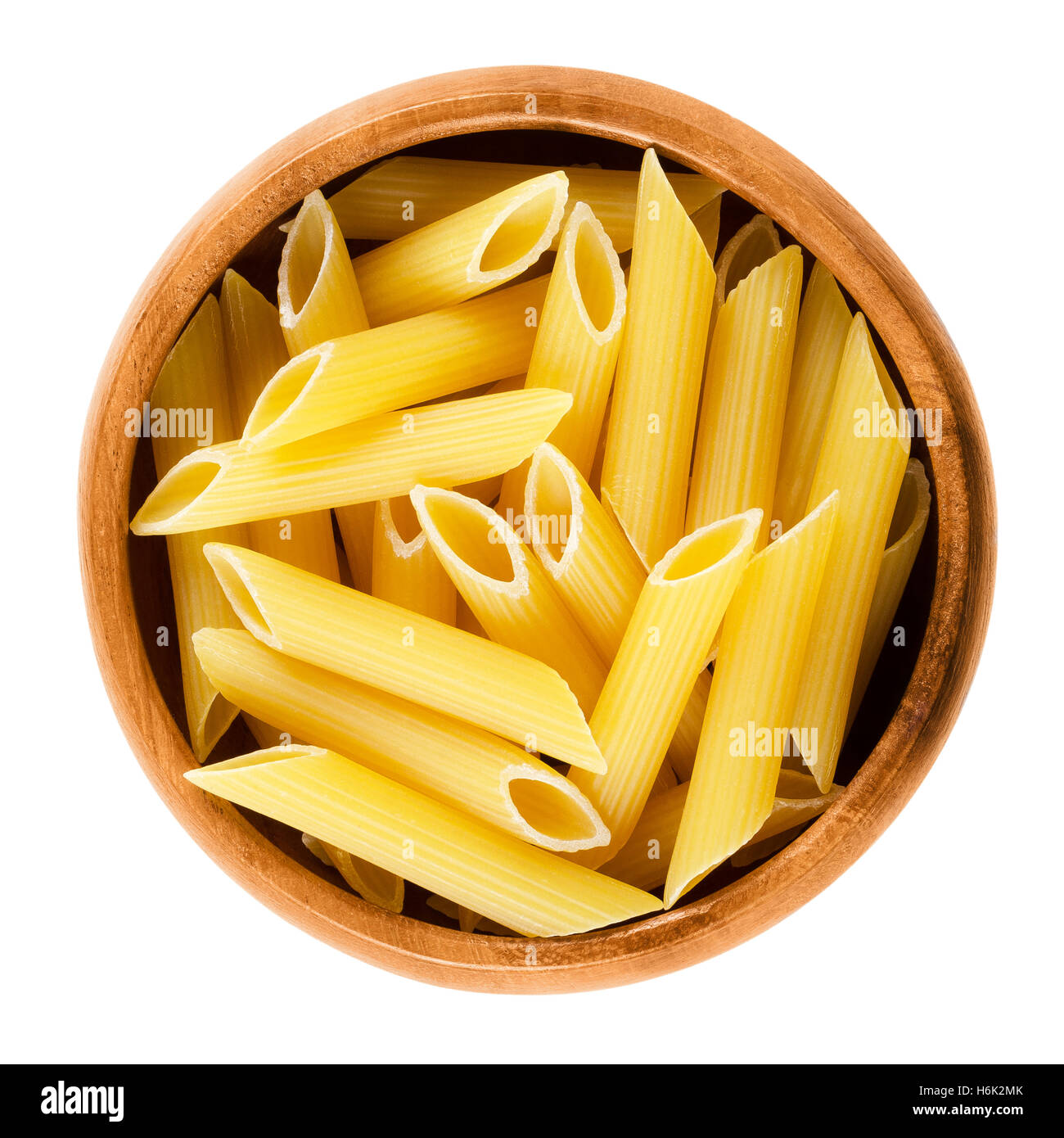 Penne rigate pasta in wooden bowl. Uncooked dried durum wheat semolina noodles. Short-cut medium length tubes with - Stock Image