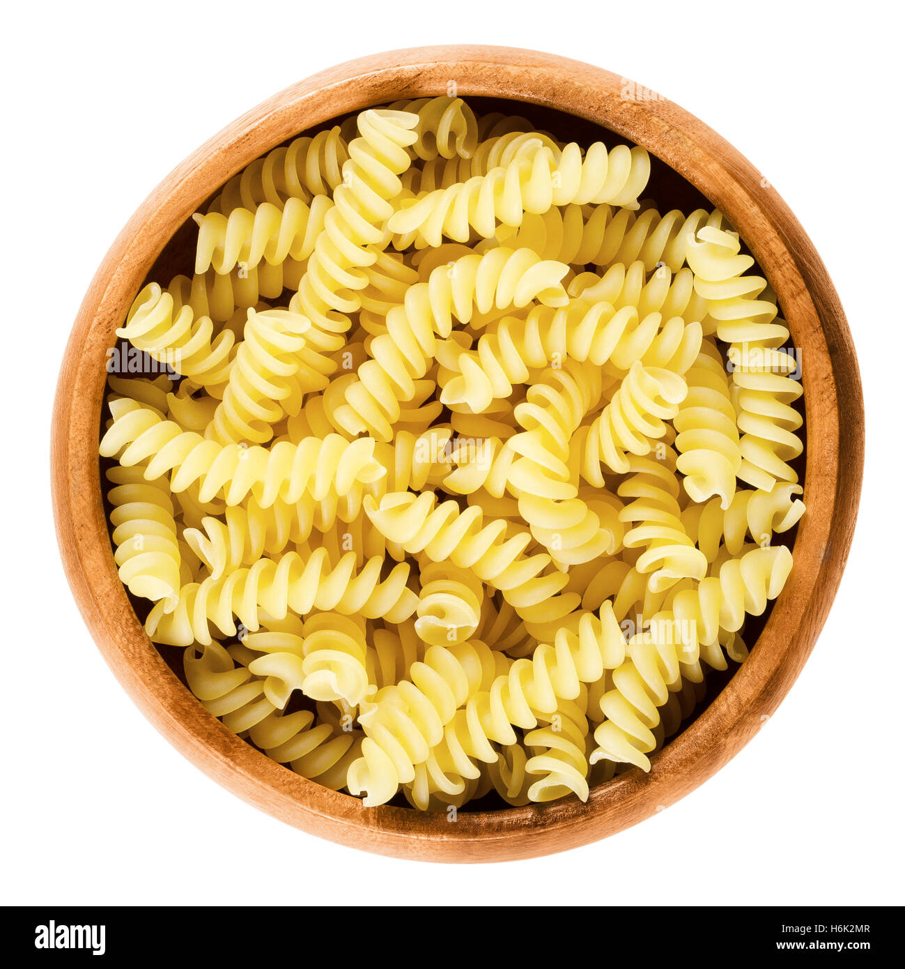 Girandole torsades pasta in wooden bowl. Uncooked dried durum wheat semolina pasta. Single S-shaped strand of noodles - Stock Image