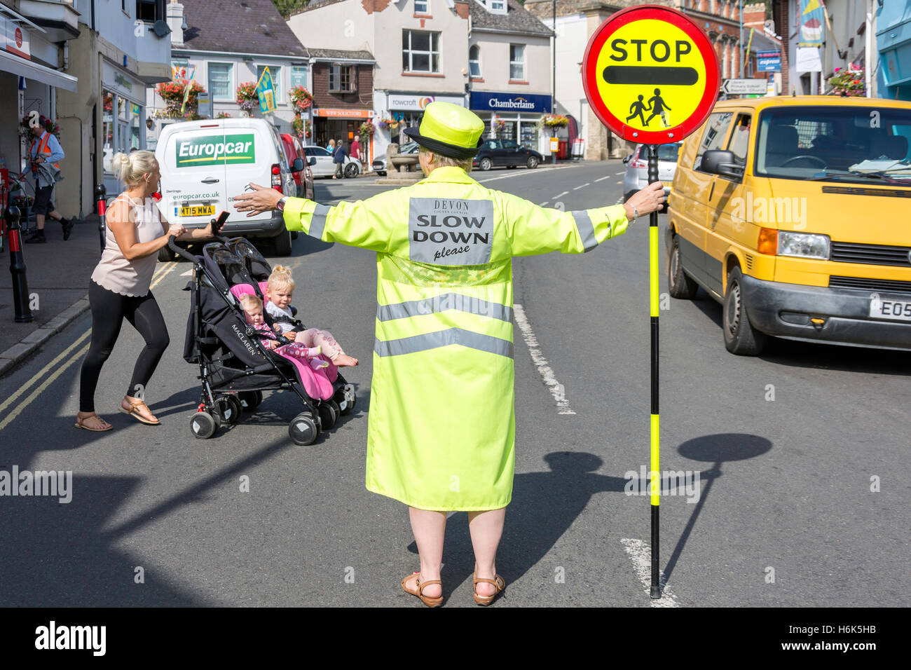 Lollipop lady (school crossing patrol officer) stopping traffic on Fore Street, Bovey Tracey, Devon, England, United - Stock Image