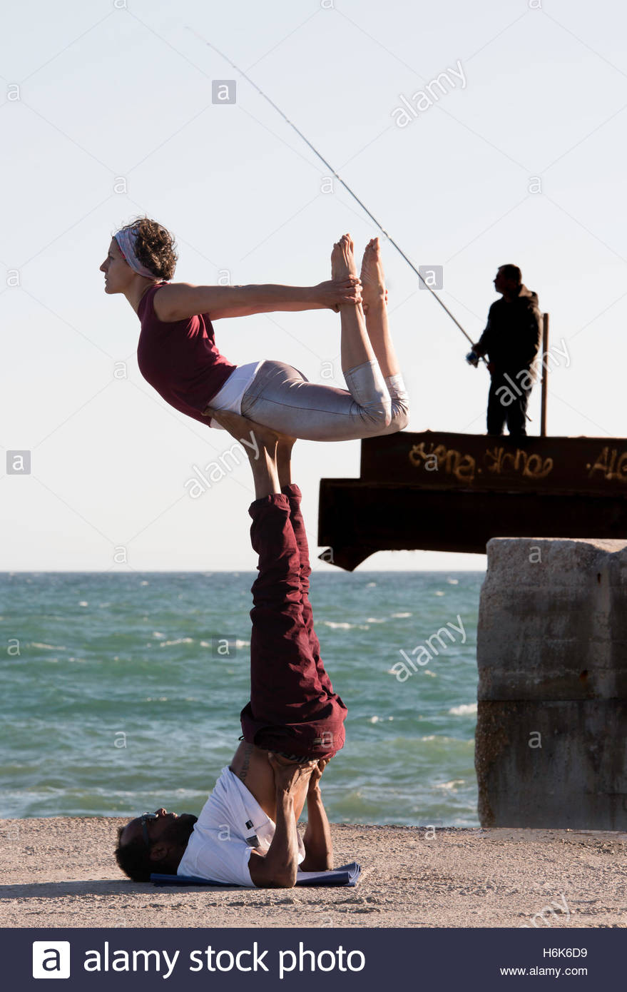 A COUPLE PERFORMS POSSESSION OF ACROYOGA NEXT TO A HARBOR - Stock Image