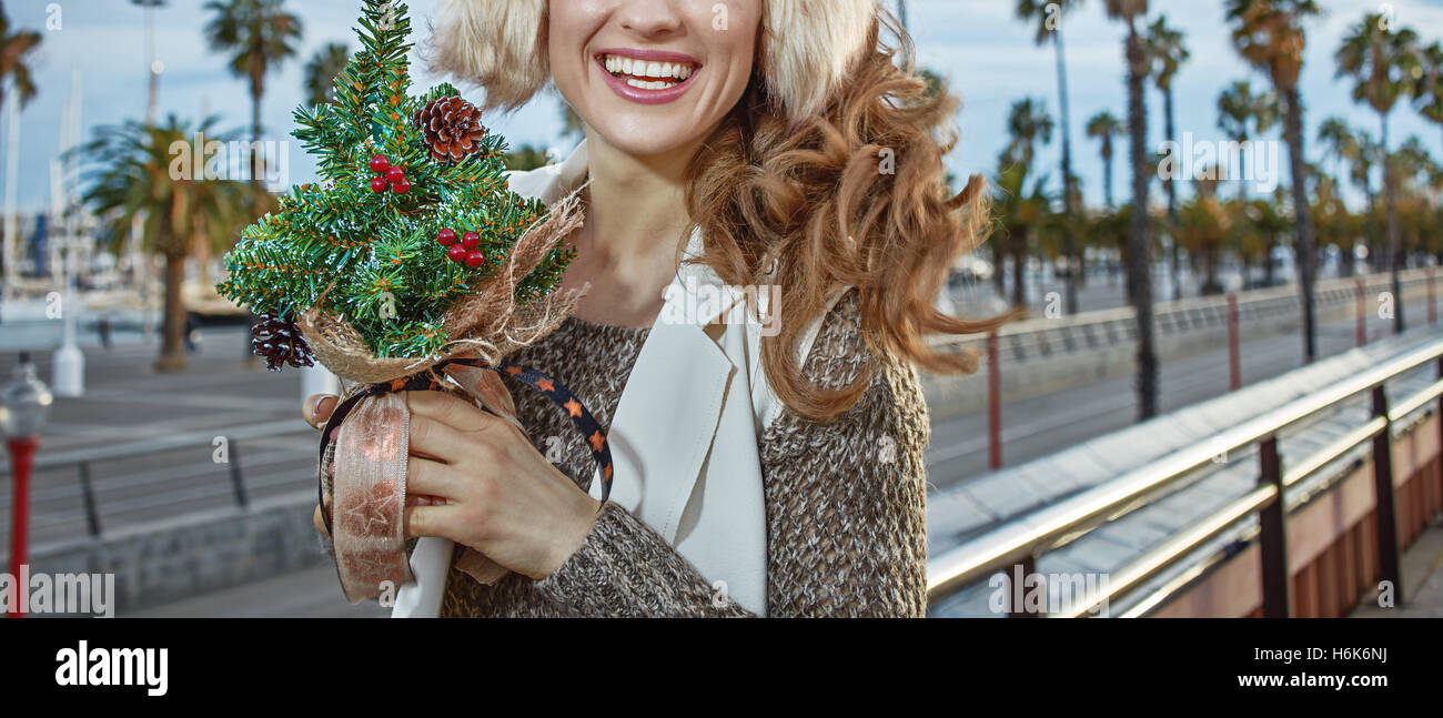 Winter wonderland in Barcelona at Christmas. Closeup on happy trendy traveller woman in Barcelona, Spain with a - Stock Image