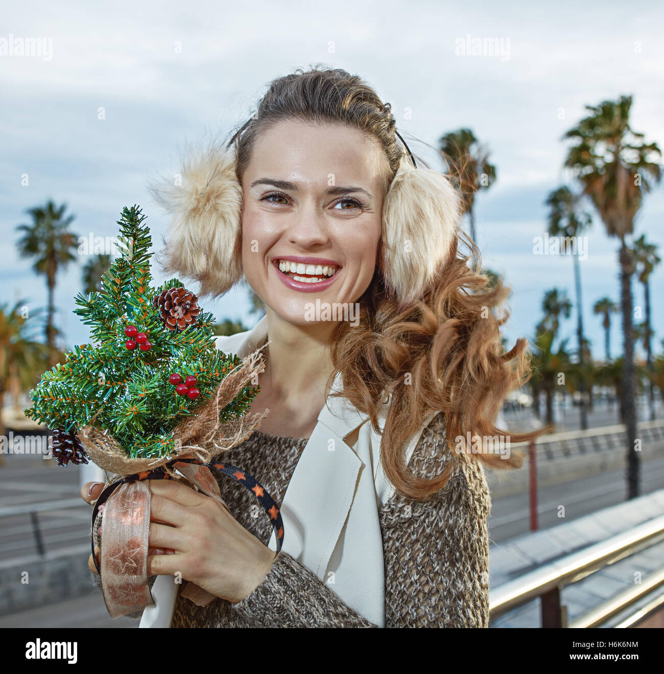 Winter wonderland in Barcelona at Christmas. Portrait of happy trendy traveller woman in Barcelona, Spain with a - Stock Image