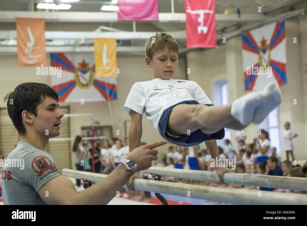 Russian gymnast Nikolai Kuksenkov (left) participates in a master class in gymnastics for children - Stock Image