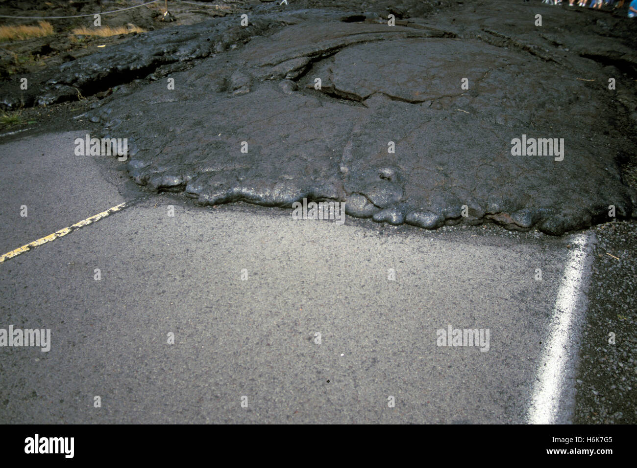 Lava from Mauna Loa volcano covers a road in Volcanoes National Park, Hawaii, Hawaii, United States - Stock Image