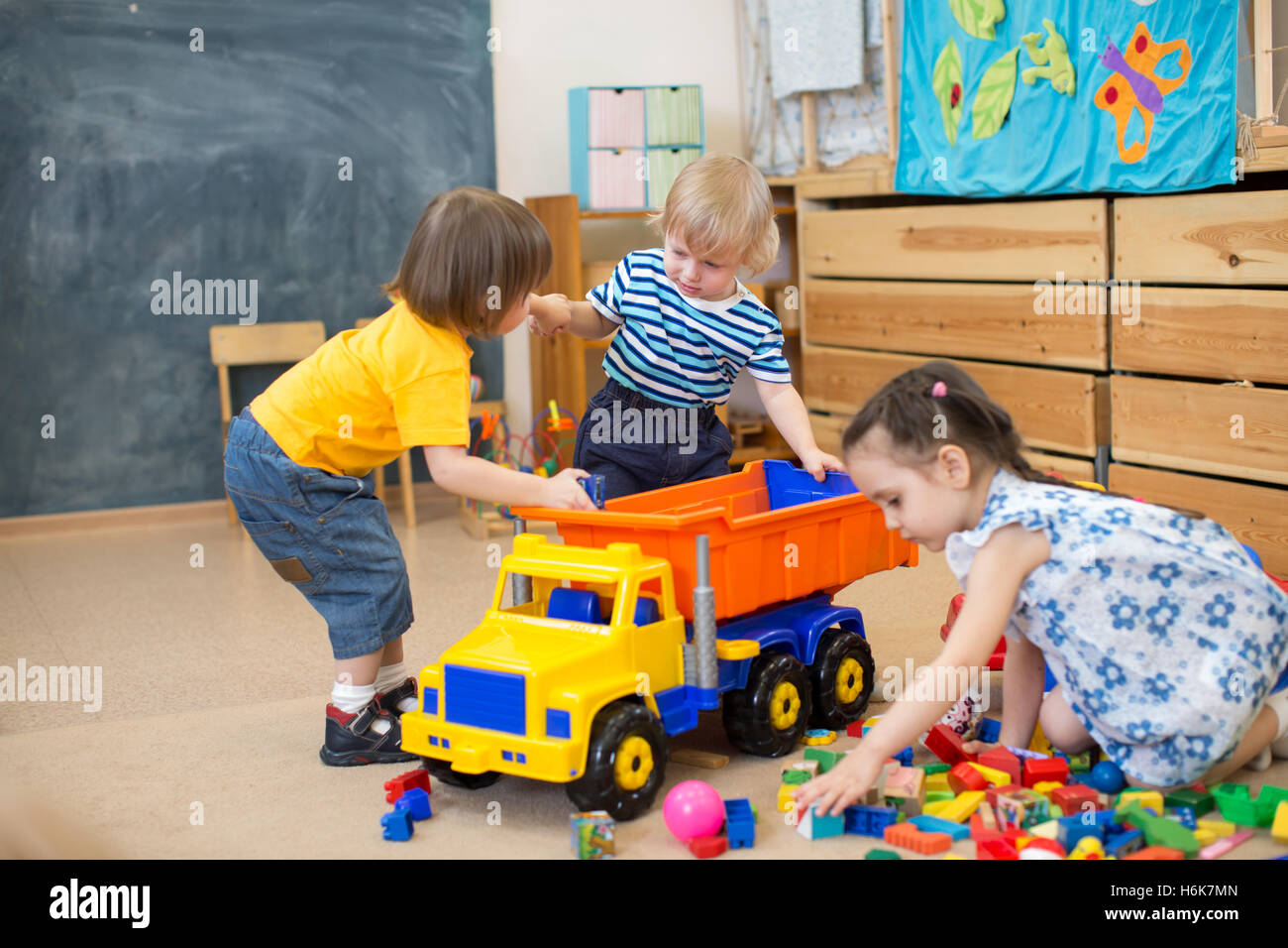 two kids conflict for toy truck in kindergarten - Stock Image