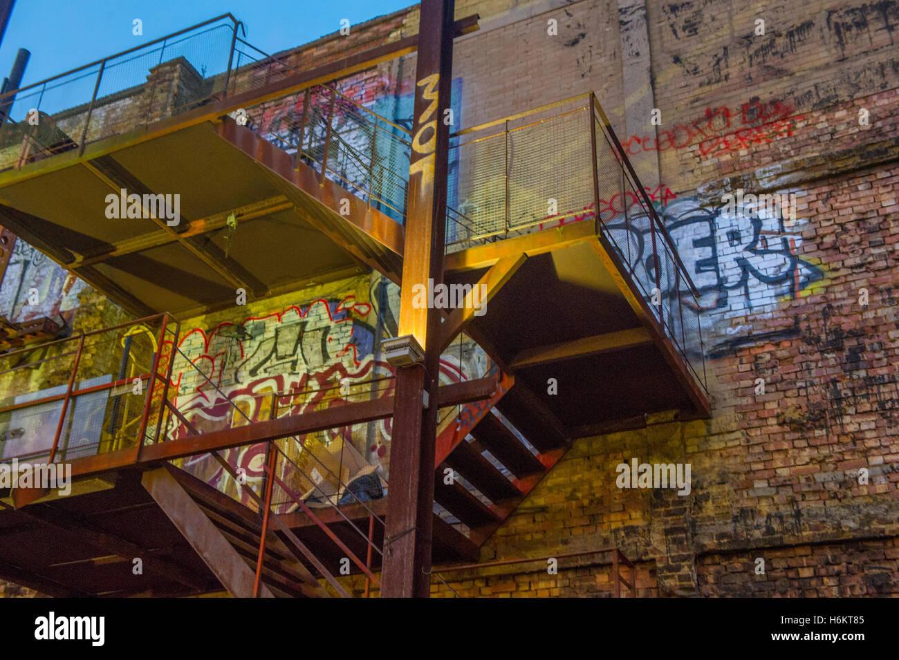 Graffiti and fire escape in a block of flats - Stock Image