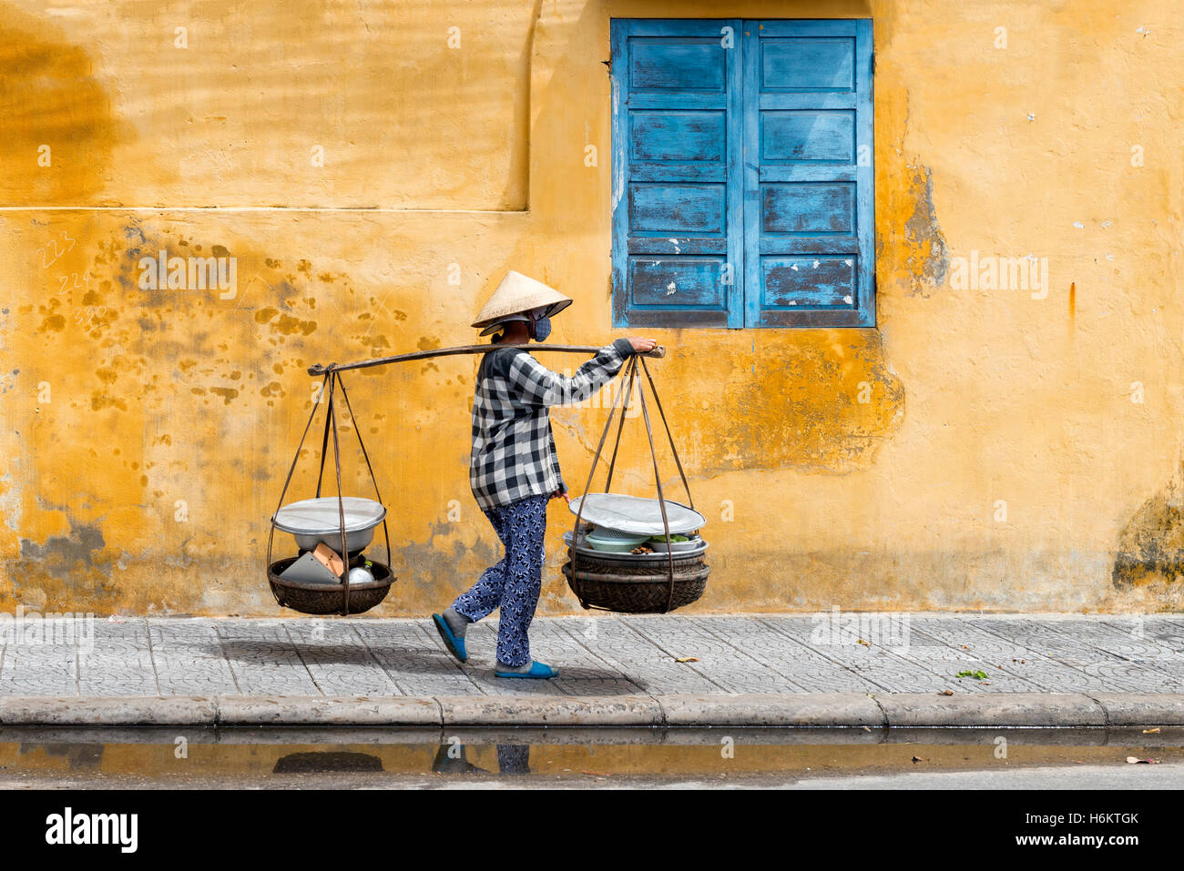 Vietnamese woman carrying a yoke in Hoi An - Stock Image