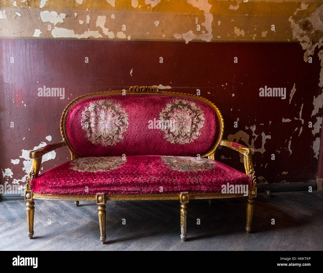 Old antique red sofa with gold gilt legs and ornate decoration - Stock Image