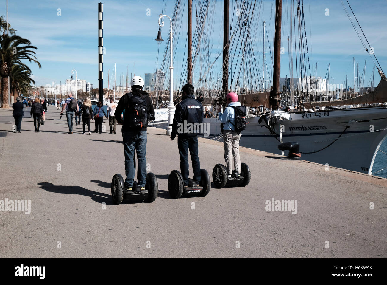 Three travellers using Segway two wheeled vehicles along Port Vell, Barcelona, Spain - Stock Image