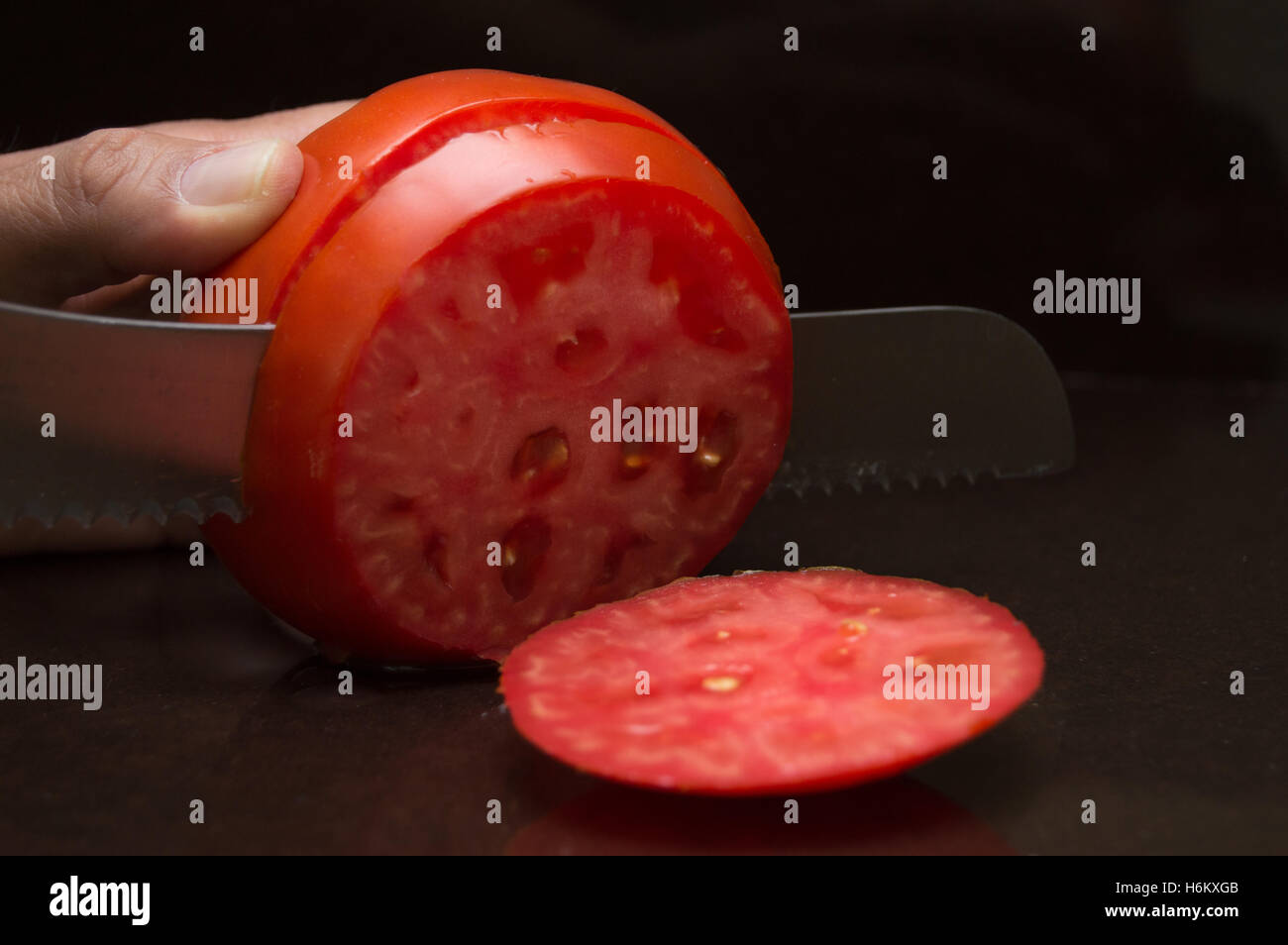 Close Up of Person Slicing a Large, Ripe, Organic Tomato with a Serrated Knife on a Dark Brown Counter Top - Stock Image